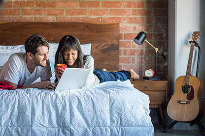 young couple in apartment researching earthquake insurance on their laptop